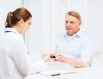 Kvinnlig doktor eller sjuksköterska som mäter värde för blodsocker Arkivfoton