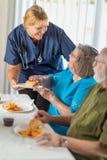 Kvinnlig doktor eller sjuksk?terskan Serving Senior Adult kopplar ihop ett m?l arkivfoton