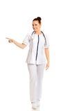 Kvinnlig doktor för full längd som pekar till det vänstert Arkivbilder