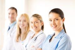 Kvinnlig doktor framme av den medicinska gruppen arkivbild