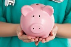 Kvinnlig doktor Holding Piggy Bank Arkivbild