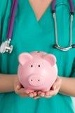 Kvinnlig doktor Holding Piggy Bank Arkivbilder