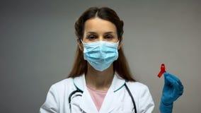 Kvinnlig doktor i den skyddande maskeringen som visar det röda bandet, låg immunitet, HIV-HJÄLPMEDEL royaltyfria foton