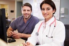 Kvinnlig doktor With Male Nurse som arbetar på sjuksköterskastationen royaltyfria bilder