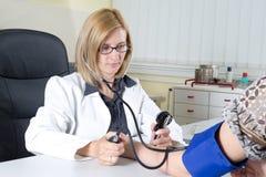 Kvinnlig doktor Measuring Blood Pressure av en patient i konsulterande rum Royaltyfri Fotografi