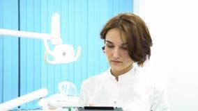 Kvinnlig doktor med anseende för minnestavlaPCdator i medicinskt kabinett-, sjukvård-, teknologi- och medicinbegrepp close upp lager videofilmer