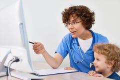 Kvinnlig doktor med barnet i regeringsställning arkivbild