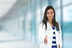 Kvinnlig doktor med den öppna handen som är klar för handskakning i sjukhus royaltyfri foto