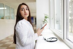 Kvinnlig doktor med mobiltelefonen på ljus bakgrund Gladlynt gullig medicinare för ung kvinna arkivfoton