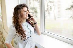 Kvinnlig doktor med mobiltelefonen p? ljus bakgrund kopiera avst?nd Gladlynt gullig medicinare f?r ung kvinna royaltyfria bilder