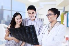 Kvinnlig doktor med patienter som ser röntgenstrålen Royaltyfri Bild