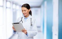 Kvinnlig doktor med stetoskop- och minnestavlaPC arkivfoto