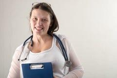 Kvinnlig doktor med stetoskopet i sjukhus Yrkesmässig praktiker för vård- klinik för medicin Medicinsk sjukvård Vit bakgrund Royaltyfria Bilder