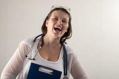 Kvinnlig doktor med stetoskopet i sjukhus Yrkesmässig praktiker för vård- klinik för medicin Medicinsk sjukvård Vit bakgrund Arkivfoto