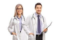 Kvinnlig doktor och en manlig doktor med en skrivplatta Arkivbilder