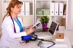 Kvinnlig doktor på skrivbordet i kontoret Fotografering för Bildbyråer