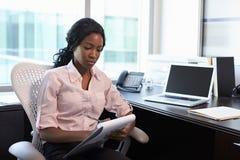 Kvinnlig doktor Sitting At Desk i regeringsställning som gör anmärkningar fotografering för bildbyråer