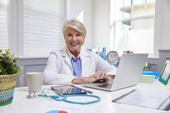 Kvinnlig doktor Sitting At Desk som i regeringsställning arbetar på bärbara datorn royaltyfri bild