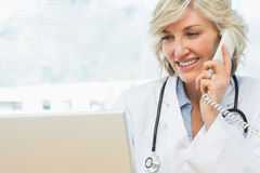Kvinnlig doktor som använder bärbara datorn och telefonen i medicinskt kontor Arkivfoto