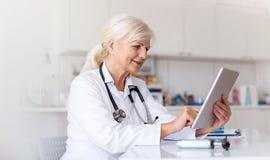 Kvinnlig doktor som använder den digitala minnestavlan i hennes kontor fotografering för bildbyråer