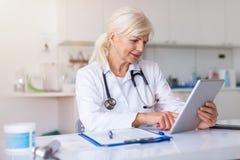 Kvinnlig doktor som använder den digitala minnestavlan i hennes kontor royaltyfri fotografi