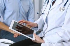 Kvinnlig doktor som använder touchpad- eller minnestavladatoren, medan konsultera manpatienten i sjukhus Medicin och sjukvård arkivbilder