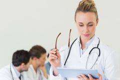 Kvinnlig doktor som använder den digitala minnestavlan Arkivbilder