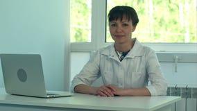 Kvinnlig doktor som arbetar på kontorsskrivbordet med bärbara datorn och ler på kameran arkivfilmer