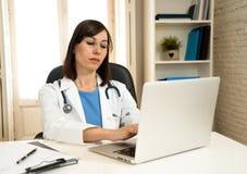 Kvinnlig doktor som arbetar på medicinsk sakkunskap och söker information på bärbara datorn på sjukhuskontoret royaltyfri fotografi