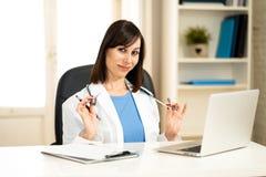Kvinnlig doktor som arbetar på medicinsk sakkunskap och söker information på bärbara datorn på sjukhuskontoret royaltyfria bilder