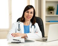 Kvinnlig doktor som arbetar på medicinsk sakkunskap och söker information på bärbara datorn på sjukhuskontoret arkivfoto