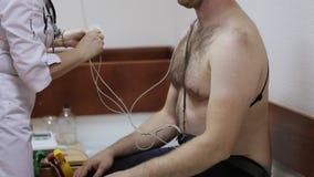 Kvinnlig doktor som fäster elektroder på tålmodig bröstkorg för ` s till daglig övervakning lager videofilmer