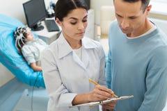 Kvinnlig doktor som frågar föräldern att sätta hans häfte Arkivfoto