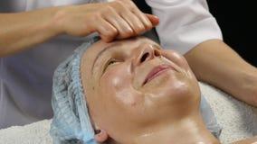 Kvinnlig doktor som gör anti--åldras massage till klienten kvinnan tycker om plast- framsidamassage i brunnsortsaton 4K lager videofilmer