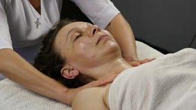 Kvinnlig doktor som gör anti--åldras massage till klienten kvinnan tycker om plast- framsidamassage i brunnsortsaton långsam röre lager videofilmer