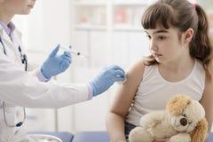 Kvinnlig doktor som ger en injektion till en ung gullig flicka arkivbilder
