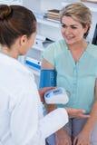 Kvinnlig doktor som kontrollerar blodtryck av en patient arkivfoton