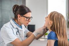 Kvinnlig doktor som kontrollerar halsen för liten flicka` s arkivbilder