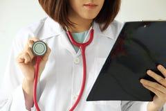 Kvinnlig doktor som läser ett tålmodigt behandlingdiagram fotografering för bildbyråer