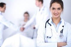 Kvinnlig doktor som ler på bakgrunden med patienten i sängen Arkivbild