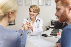 Kvinnlig doktor som ler till patienten fotografering för bildbyråer