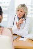 Kvinnlig doktor som lyssnar till patienten med koncentration royaltyfri fotografi