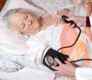 Kvinnlig doktor som mäter blodtryck Arkivfoto