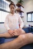 Kvinnlig doktor som masserar knäet av den manliga patienten arkivfoton