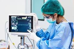Kvinnlig doktor som pekar till bildskärmen för hjärtahastighet i operationrum H arkivfoton
