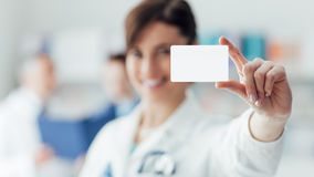 Kvinnlig doktor som rymmer ett affärskort Fotografering för Bildbyråer