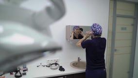 Kvinnlig doktor som sätter på framsidamaskering Den unga den brunettdoktorn eller sjuksköterskan i blått lag sätter på framsidama arkivfilmer