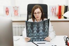 Kvinnlig doktor som sitter på skrivbordet med datoren, filmröntgenstråle hjärnan vid radiographic mri för bildct-bildläsning i lj royaltyfria foton