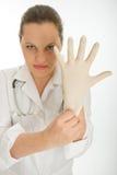 Kvinnlig doktor som sätter en latexhandske Arkivfoton