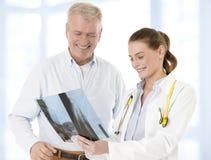 Kvinnlig doktor som talar med den höga tålmodign och visar hennes röntgenstråle arkivfoto